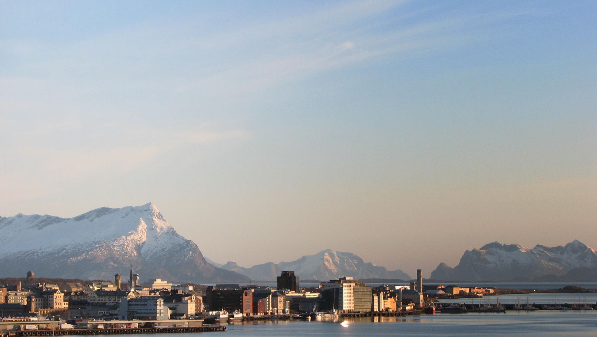 Bodø havn på en solskinnsdag med snødekte fjell i bakgrunnen